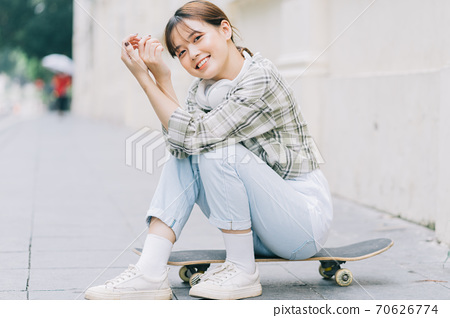Girl learning to skateboard on the street, street activities 70626774