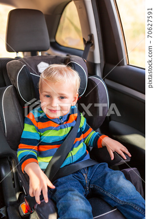 Little baby boy sitting on a car seat buckled up in the car. 70627591
