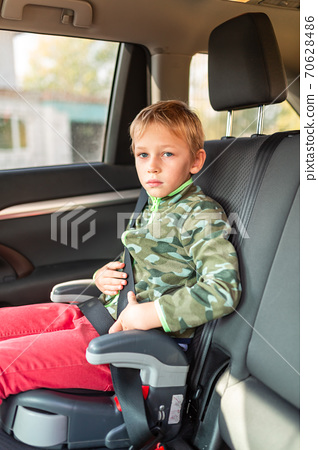 Little boy sitting on a booster seat buckled up in the car. 70628486