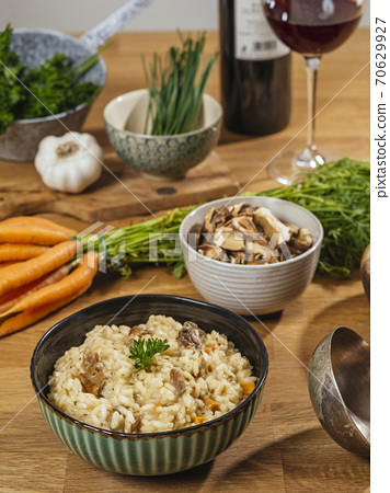 Bowl of Risotto on a table with ingredients 70629927