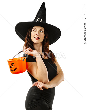 Sexy witch smiling and holding Halloween pumpkin bucket 70629928