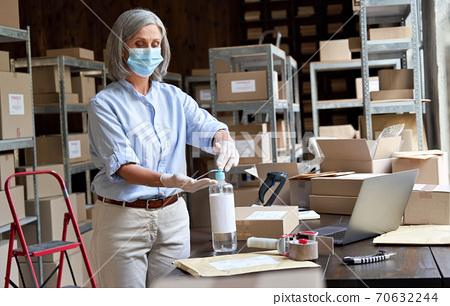 Older female entrepreneur wearing mask using sanitizer working in warehouse. 70632244