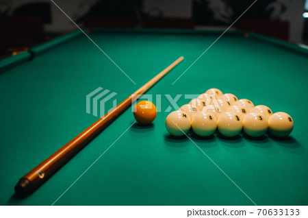 Playing pool on a green table.Balls and cue are laid out on the table 70633133