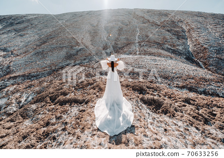 Beautiful unrecognizable bride in a wedding dress and hat on top of the salt mountains. Stunning young bride in a hat. Wedding day. Beautiful portrait of the bride without the groom. 70633256