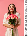 Full-length vertical portrait romantic and dreamy, sensual brunette girl in dress, holding beautiful bouquet flowers, smelling roses with closed eyes and smiling, standing happy over pink background 70633616