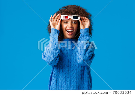 Excited happy and cheerful young woman watching movie in 3d glasses, laughing and checking screen without eyewear, impressed with cinematics and awesome special effects, standing blue background 70633634