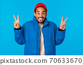 Say cheeze. Ecstatic cheerful young african american guy enjoy winter holidays, like christmas and new year, standing in padded jacket, red beanie, showing peace gestures and smiling, blue background 70633670