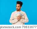 Guy got cash, thinking what buy, how waste money during winter holidays sale season. African american good-looking man with afro haircut holding dollars near chest and gazing suspicious camera 70633677