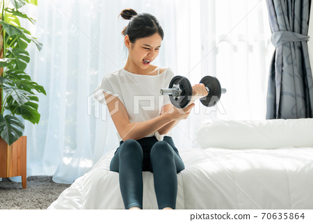 Woman sitting on the bed and doing exercises with lifting dumbbells that are too heavy. 70635864