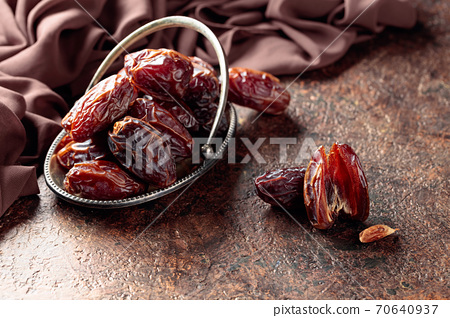Dried sweet dates on an old brown table. 70640937