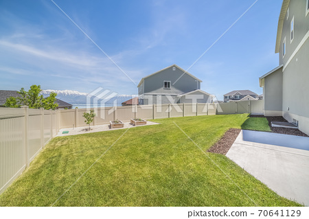 Backyard of a home with small tree and planting beds near the wooden fence 70641129