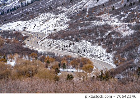 Panorama of a road that winds through an immense mountain with snow in winter 70642346