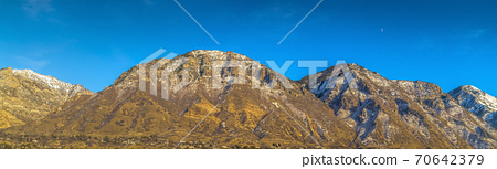 Towering mountain with a residential area near the base against deep blue sky 70642379
