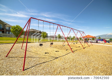 Park with swings pavilion and slides in front of homes and lake on a sunny day 70642560