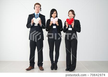 三名年轻的男性和女性操作员穿着西装与心(全身) 70642974