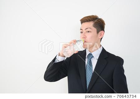 一个穿着西装的年轻人努力地从宠物瓶里喝水 70643734