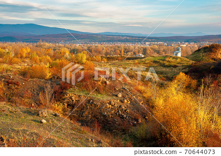 rural valley at sunset. beautiful autumn landscape in mountains. village in the distant valley. clouds on the blue evening sky 70644073