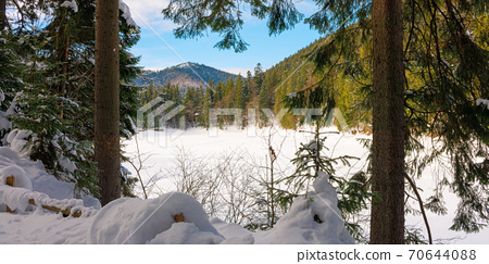 snow covered mountain lake among the forest. green spruce trees on the shore. beautiful sunny weather. clouds on the sky 70644088