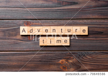 Adventure time word written on wood block. Adventure time text on cement table for your desing, concept 70649386