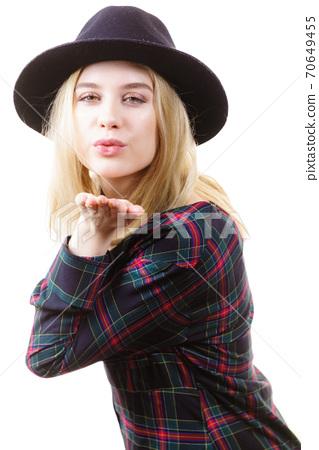 Woman in hat sending air kiss 70649455