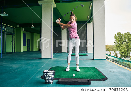 Concentrated sportswoman teeing off with a driver 70651298
