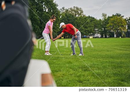 Experienced male tutor instructing a female beginner 70651319