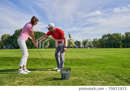 Beginner female golfer learning a proper golf grip 70651953