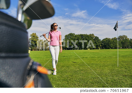 Slim lady carrying an iron golf club 70651967