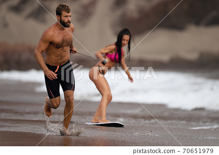 A young man pulls a young girl on a rope who is learning a skimboard 70651979