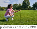 Sportswoman preparing to play a game of golf 70651994