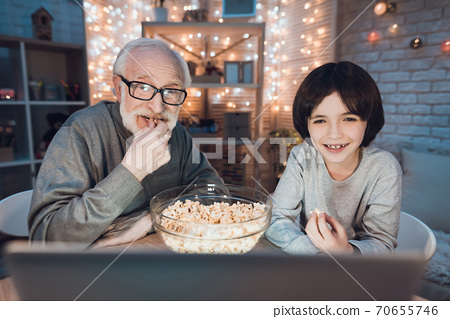 Boy with grandfather watching night movies. 70655746