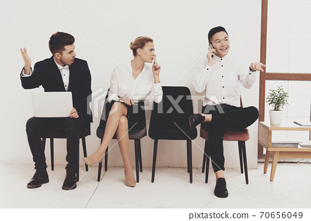 A man talks loudly while sitting in the office. 70656049