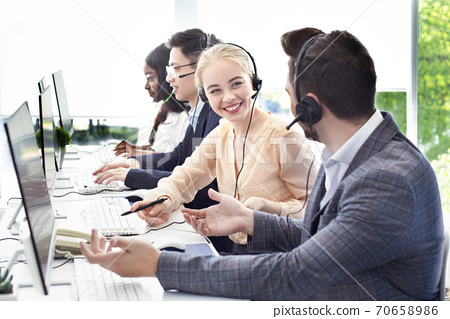 Smiling customer support workers communicating to solve client's problem together at call centre office 70658986