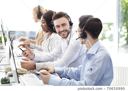 Happy male technical support operators having friendly chat at call centre 70658990