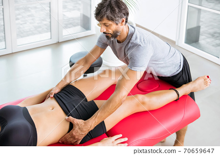 Osteopath performing a pelvis alignment assessment 70659647