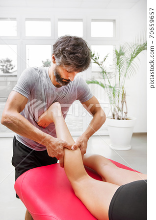 Male osteopath performing calf myofascial massage 70659657