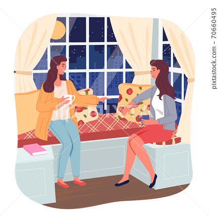 Two girlfriends sitting near window at night and talking with cup of tea or coffee, sitting at couch 70660495