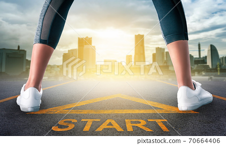 Woman runner is standing on a start sign ready to run to goal and freedom on modern city for motivation begining concept. 70664406