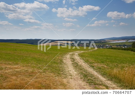 Country dirt road through farmlands 70664707