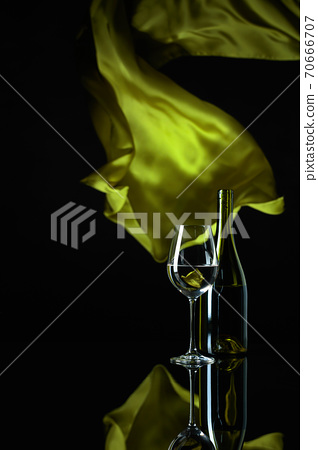 Wineglass and bottle of white wine on a black reflective background. 70666707