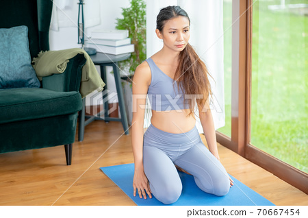 Pretty Asian girl action of different yoga posture in living room of house with green garden 70667454