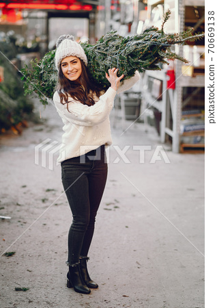 Cute brunette in a white sweater with Christmas tree 70669138