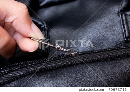 Hand fastening the zip on the bag 70678711