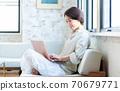 一名中年妇女在客厅里操作电脑 70679771