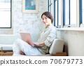 一名中年妇女在客厅里操作电脑 70679773