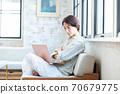 一名中年妇女在客厅里操作电脑 70679775