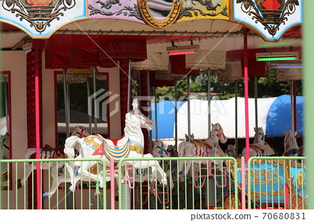 A merry-go-round that is fun to go around in an amusement park 70680831