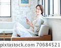 做智能手机的中年妇女在客厅 70684521