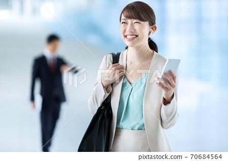통근하고있는 여성이 스마트 폰에서 음악을 듣고있다 70684564