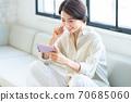 中年妇女在她的智能手机上观看视频 70685060